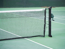 Tennis net and post. Close-up of tennis net with post and handle on green hard court Royalty Free Stock Images