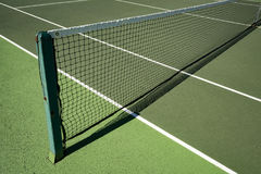 Tennis net strung across artificial hardwearing tennis court. Tennis net in sunshine on all weather tennis court Royalty Free Stock Photos