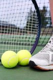 Tennis objects with player leg. Tennis shoe, racket and balls on a hard court in fron tof net Stock Image