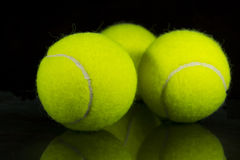 Tennis and paddle three yellow balls. Over black background and reflection Stock Photos