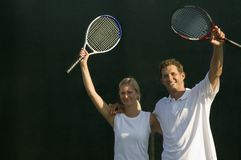Tennis Partners Raising Rackets Stock Photography