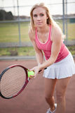 Tennis player. A beautiful caucasian tennis player serving the ball on the tennis court Stock Photography