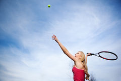 Tennis player. A beautiful caucasian tennis player serving the ball on the tennis court Royalty Free Stock Photos