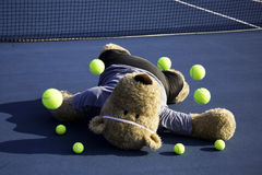 Tennis Player. Oversized teddy bear dressed as a tennis player laying on tennis court with raquet and balls bouncing in air stock photos