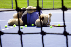 Tennis Player. Oversized teddy bear dressed as a tennis player laying on tennis court with raquet and balls royalty free stock image