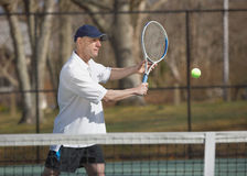 Tennis player. Handsome man tennis player at court hitting ball Royalty Free Stock Photography