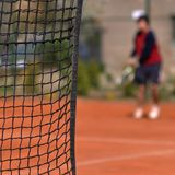 Tennis player. A tennis player behind the net royalty free stock photography