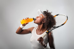 Tennis player. Young attractive black tennis player drinking an energy drink Stock Photos