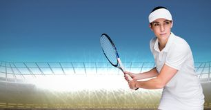 Tennis player against bright lights with blue sky Royalty Free Stock Image