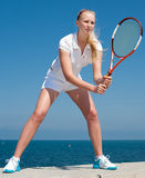 Tennis-player on background of the sky. Young blond  tennis-player with tennis racket in white sportwear is standing on seashore Stock Photography