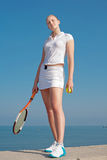Tennis-player on background of the sky. Young blond  tennis-player with tennis racket and tennis balls in white sportwear is standing on seashore Stock Photography