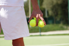 Tennis player with balls in hand Royalty Free Stock Image