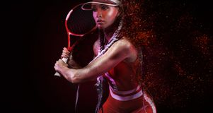 Tennis player. Beautiful woman athlete with racket in red costume and hat isolated on black background. Fashion and stock photo
