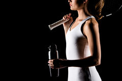 Tennis player with bottle. Partial view of female tennis player holding sport bottle and tennis racquet on black stock photography