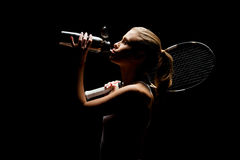 Tennis player with bottle. Young female tennis player holding racquet and drinking on black stock photo