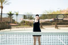 Tennis player celebrating her win. Tennis player celebrating her success after winning with her arms outstretched and looking up at sky smiling Stock Image