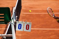 Tennis Player on a Clay Court with Umpire Chair. Tennis player umpire chair with scoreboard and racket on a clay court in the beginning of the game Stock Photo