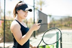 Tennis player on court social networking. Pretty young female tennis player on court using smart phone during a break in training Stock Image
