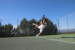 Tennis player dives to catch a ball Royalty Free Stock Images