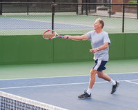 Tennis player finishing running volley. Stock Photography