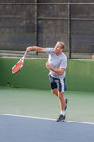 Tennis player finishing service motion. Royalty Free Stock Photo
