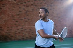 Tennis player giving a backhand swing on tennis court. An African American Tennis player giving a backhand swing on tennis court Stock Photo