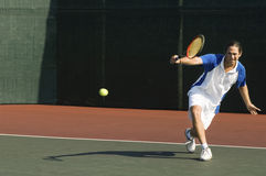 Tennis Player Hitting Backhand On Court. Full length of a male tennis player hitting backhand on the tennis court Stock Photos