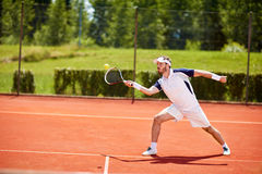 Tennis player hitting ball. Tennis player on tennis court hitting ball Royalty Free Stock Image