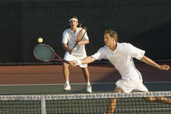 Tennis Player Hitting Ball With Doubles Partner Standing In Background. Young male tennis player hitting ball with doubles partner standing in background Stock Photos