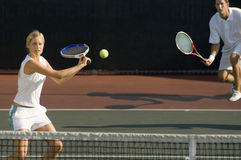 Tennis Player Hitting Ball With Partner Standing In Background. Young female tennis player hitting ball with doubles partner standing in background Royalty Free Stock Photography