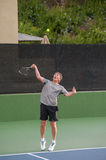 Tennis player hitting his serve. Tall Baby Boomer focused on ball toss Stock Image