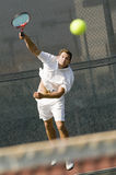 Tennis Player Hitting A Shot On Court. Full length of young male tennis player hitting a shot on court Royalty Free Stock Photos