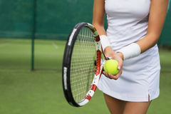 Tennis player holding racket and ball in hands Royalty Free Stock Images