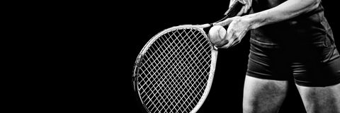 Tennis player holding a racquet ready to serve. On black background Stock Photos