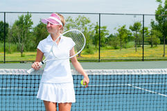 Tennis player holding tennis racket and ball on the tennis court royalty free stock image