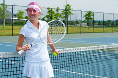 Tennis player holding tennis racket and ball on the tennis court royalty free stock photos
