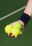 Tennis player holding three balls Stock Images
