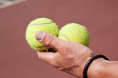 Tennis-player holding two balls in his hand Royalty Free Stock Photos