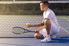 Tennis player kneeling in font of net holding racket and ball stock images