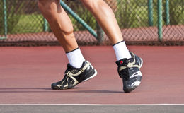 Tennis player legs and feet on court Royalty Free Stock Image
