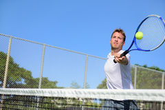Tennis player man hitting ball in a volley. Male sport fitness athlete playing tennis on outdoors hard court in summer. Healthy active lifestyle concept Stock Photo