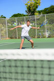 Tennis player - man hitting forehand playing. Outside on hard court. Male sport fitness athlete practicing in summer outdoors living healthy active lifestyle Stock Photos