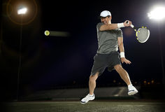 Tennis player during a match. Tennis player during a night match with dark background Stock Images