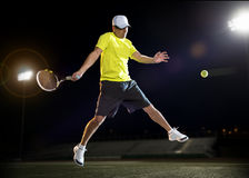 Tennis player at night. Tennis player hiting the ball during a match at night Royalty Free Stock Photo