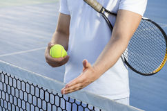 Tennis player offering hand handshake on net Stock Photo