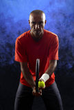 Tennis player portrait. A portrait of a tanned sportive tennis player with a racket against blue and black background. tennis player portrait Royalty Free Stock Image