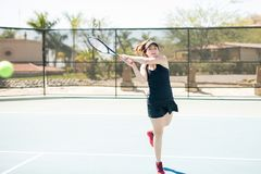 Tennis player practicing hard to improve her game. Latin female tennis player hitting the ball with a backhand, training hard to improve her game Royalty Free Stock Photography