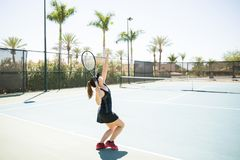 Tennis player practising on court. Fit young female tennis player serving ball whilst practising on court Stock Photography