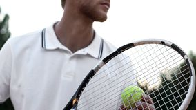 Tennis player preparing to serve ball on court, sports competition, close-up. Stock photo royalty free stock image