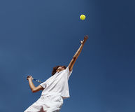Tennis player with racket during a match game. Tennis player with racket during a serve in match game isolated on blue sky Stock Image